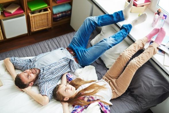 vader en dochter liggen op de bank naast elkaar