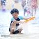 kind speelt met water aan zee