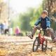 jongen fietst buiten over de herfstbladeren
