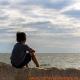jongetje kijkt uit over zee