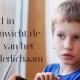 kind trekt zich terug en kijkt verlegen