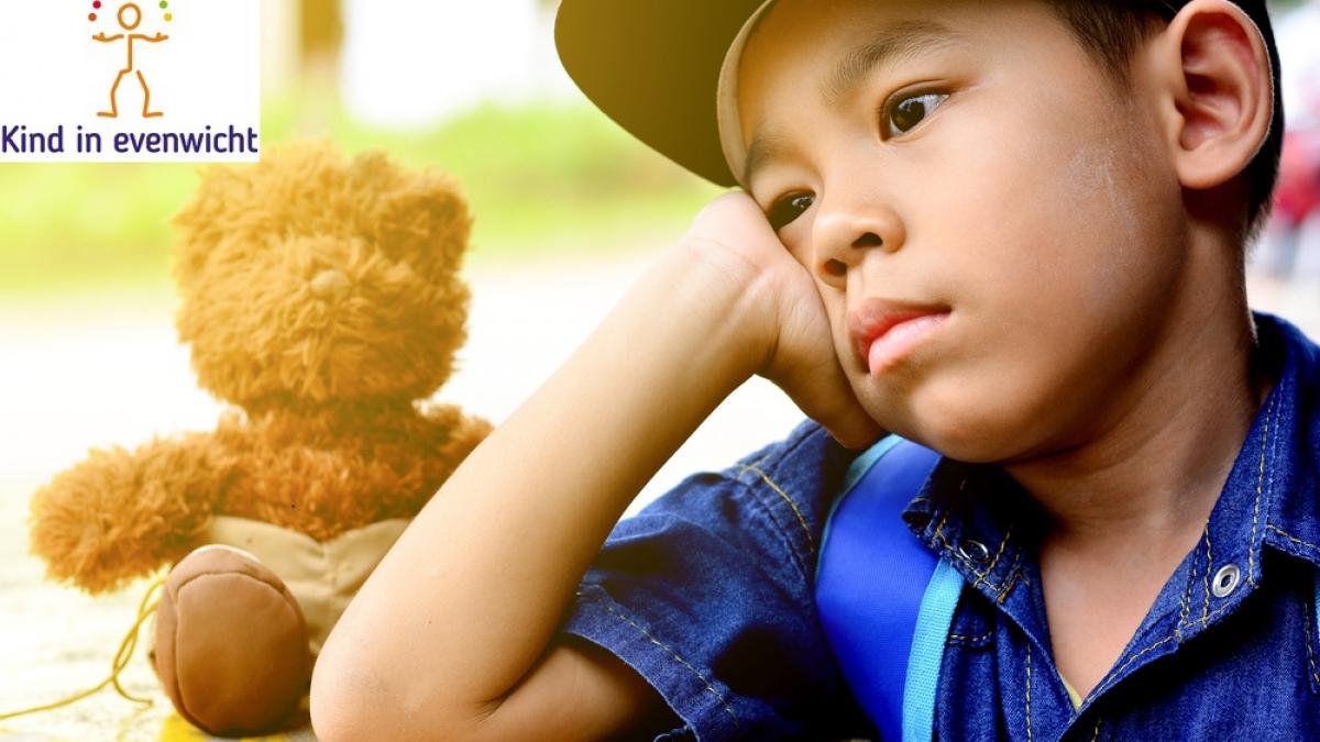 kind kijkt dromerig en zit naast zijn speelgoedbeer