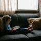 meisje leest zittend op de bank een boek